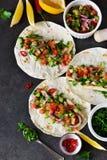 与填装和鳄梨调味酱捣碎的鳄梨酱调味汁的墨西哥炸玉米饼 免版税库存照片