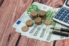 与墨水笔,硬币的100欧元票据 免版税图库摄影