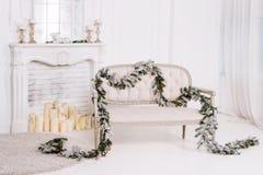 与壁炉、沙发和圣诞节装饰的白色经典内部 图库摄影
