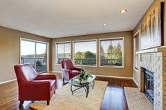 与壁炉和两把红色扶手椅子的舒适客厅内部 免版税图库摄影