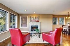 与壁炉和两把红色扶手椅子的舒适客厅内部 库存图片
