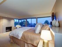 与壁炉和出口的可爱的卧室设计对露台 库存图片