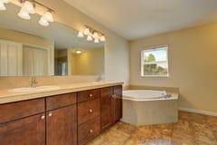 与壁角浴盆和大理石地板的巨大卫生间内部 库存照片