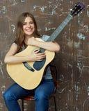 与声学吉他的微笑的少妇画象 免版税库存图片