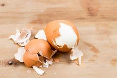 与壳的水煮蛋在木桌上剥了皮 图库摄影