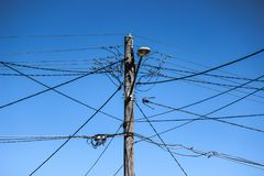 与复杂接线、街灯和蓝天的高压电杆 库存照片
