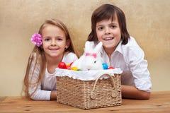 与复活节兔子和五颜六色的鸡蛋的愉快的孩子 免版税库存照片