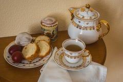 与复活节蛋糕、鸡蛋、茶壶和一杯茶的静物画 库存图片