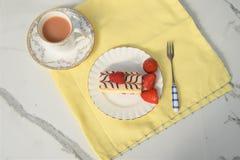 与夏时新鲜的奶油色切片蛋糕的平的位置用草莓和茶 免版税库存照片