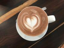 与外卖心脏的图片的热奶咖啡咖啡在一块玻璃在手上,顶视图的 免版税库存图片