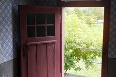 与外面绿色灌木的老开放红色门 库存照片