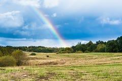 与多云天气,在一个斜切的黄色领域的大多雨云彩的秋天风景,彩虹在天空 库存照片