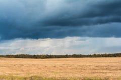 与多云天气,在一个斜切的黄色领域的大多雨云彩的秋天风景 库存图片
