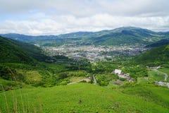 与多云天空的豪华的绿叶山风景全景和镇视图 库存图片