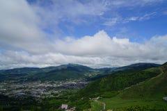 与多云蓝天的豪华的绿叶山风景全景和镇视图 库存照片