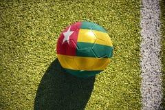 与多哥的国旗的橄榄球球在领域说谎 免版税库存图片