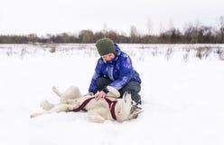 与多壳的狗戏剧的妇女所有者在雪在冬日 库存图片