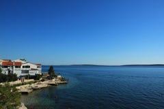 与多岩石的海滩手段和蓝色海的沿海看法 免版税库存照片