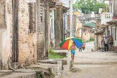 与多彩多姿的伞的女性孩子走在特立尼达古巴的街道上的 免版税图库摄影