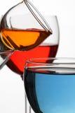 与多彩多姿的液体的玻璃酒杯在白色背景 库存图片