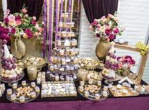 与多彩多姿的玫瑰的婚礼装饰在花瓶,柔和的淡色彩上色了杯形蛋糕、蛋白甜饼、松饼和macarons 免版税图库摄影