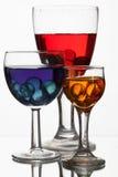 与多彩多姿的液体的玻璃酒杯在一白色backgrou 免版税库存图片