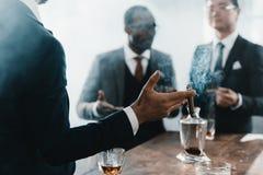 与多文化企业队的商人抽烟的雪茄 库存图片