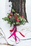 与多汁植物和绯红色花的土气婚礼花束在树旁边的雪 户外 附庸风雅 免版税库存图片