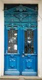 与多灰尘的城市的老蓝色门 库存图片