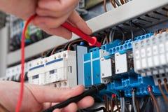 与多用电表探针的电工审查的fusebox 免版税库存照片