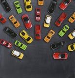 与多辆玩具汽车的交通堵塞概念在黑板 免版税库存照片