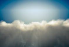 与多雨云彩的背景由太阳点燃了在蓝色 图库摄影