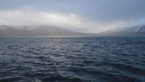 与多雪的山峰的全景山在蓝色海和多云天空背景中 股票视频