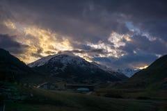 与多雪的山的日落 库存照片