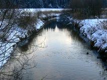 与多雪的岸的小溪 免版税库存图片