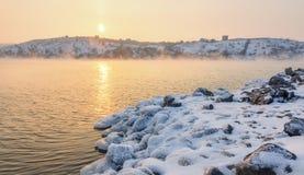 与多雪的石头的冬天风景在美丽的河 库存图片
