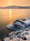 与多雪的石头的冬天风景在美丽的河 免版税库存图片