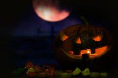 与夜月亮和糖果的愉快的万圣夜南瓜卡片背景 免版税库存照片