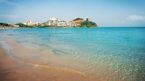 与大厦的夏天蓝色沿海在背景的海滩和植被 免版税图库摄影