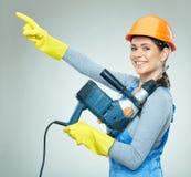 与大厦的微笑的妇女建造者用工具加工在拷贝的pointinf手指 免版税库存照片