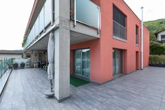 与大大阳台和玻璃栏杆的红色修造的外部 免版税库存图片