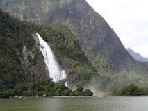 与大河和森林的瀑布Milford Sound的,新西兰 免版税图库摄影