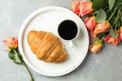 与大理石盘子、咖啡,新月形面包和玫瑰的构成在灰色背景 库存图片