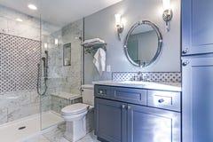 与大理石阵雨周围的新的蓝色卫生间设计 库存照片