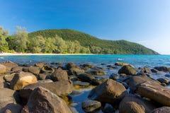 与大石头的白色沙滩海湾在前景和森林 免版税库存照片