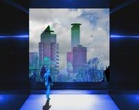与大窗口在地平线和年轻人的图的超现实的蓝色内部 图库摄影