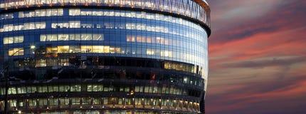 与大窗口的现代办公楼在晚上 免版税库存图片