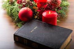 与大红色蜡烛和圣诞节的圣经 库存图片