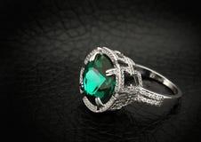 与大绿色宝石的首饰圆环在黑皮革背景 免版税图库摄影