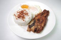 与大蒜炒米、荷包蛋和烂醉如泥的番木瓜Daing Silog的油煎的Daing na Bangus 图库摄影